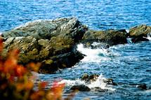 Waves splashing on rocks in ocean.