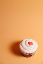 Valentine's cupcake with red heart on orange background.