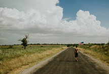 a boy child walking outdoors on a rural road carrying an American flag