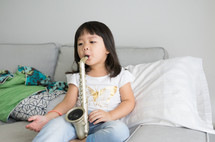 a child playing with a toy saxophone
