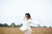 a woman twirling in a field