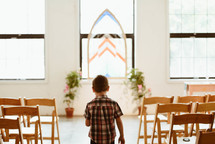 a boy walking in an empty church