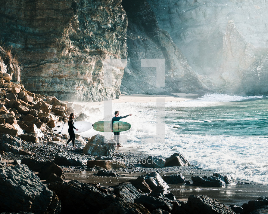 surfers on a rocky beach