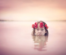 child with a crown of flowers in water