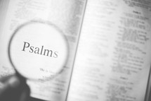 magnifying glass over Psalms in an open Bible
