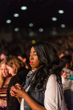 African American young woman in an audience praying