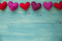 felt heart border on teal wood background.