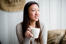 A young woman holding a cup of coffee.