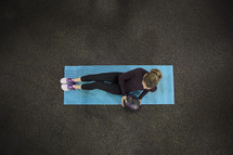 woman on a mat with a medicine ball
