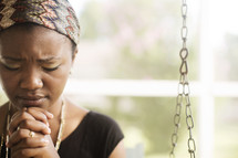 African-American teen sitting outside on a porch swing praying.