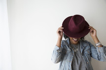 a woman covering her face with a hat