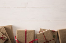 Gifts wrapped in brown paper and red ribbon on a white table.