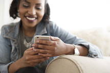 An African American woman sitting on a couch checking her cellphone