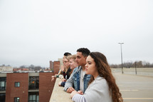 group of teens looking over a railing on a parking deck