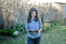 A woman standing outside reading the Bible
