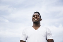 A smiling man against a cloudy white sky.