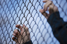 hand on a chain link fence