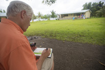 artist using pastels to sketch a tropical cabin