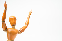 wooden mannequin with raised hands
