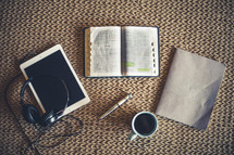 headphones, tablet, open Bible, pen, journal, and coffee cup