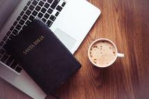 Santa Biblia, laptop, and cappuccino