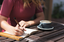 a woman writing in a journal over coffee