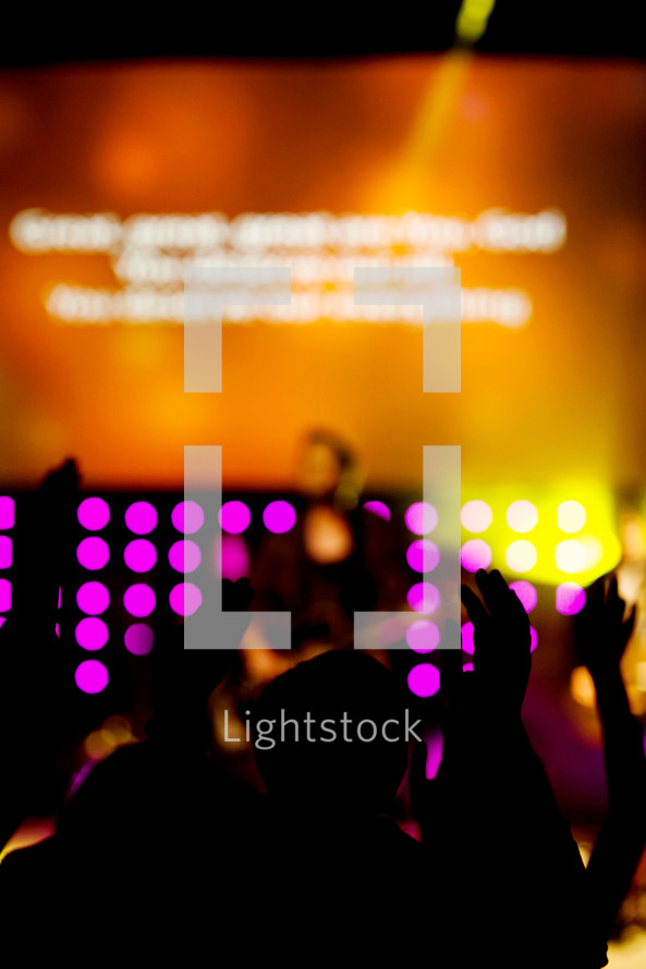 Silhouette of people with hands raised facing lighted stage during worship service
