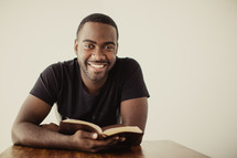man reading a Bible and smiling