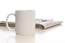 coffe mug, newspaper, and reading glasses