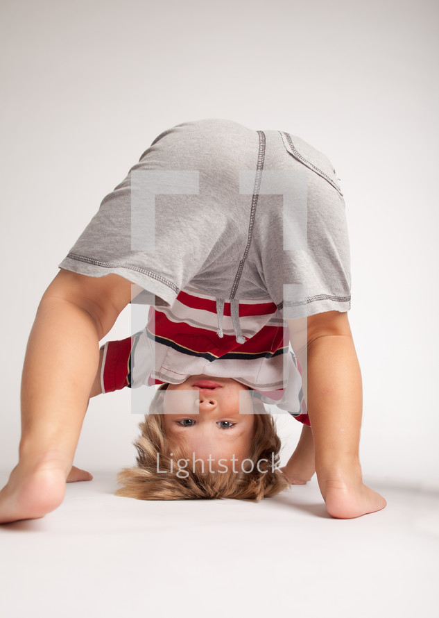 little boy doing a head stand