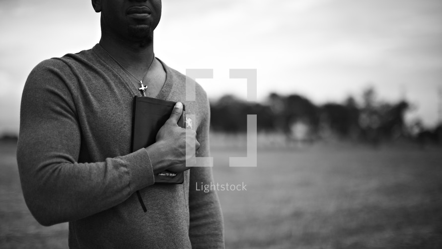 A man holding a bible over his heart