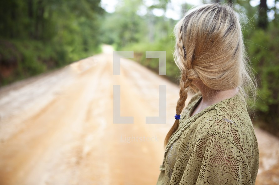 Woman looking at open dirt road