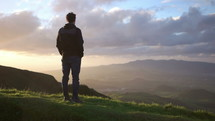 man standing on a mountaintop looking out at a sunrise