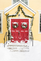 garland and wreaths on red doors