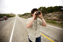 A man looking through a lens on a highway road