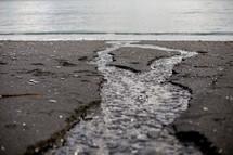A rivulet runs through a sandy beach to the sea.