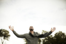 An African American man raising his hands in worship