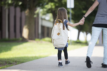 A mother and daughter holding hands and walking to school.