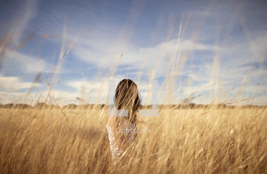 Girl sitting in wheat field