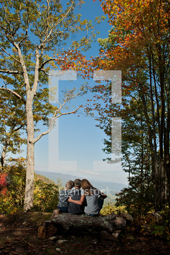 family sitting on a fallen tree overlooking a mountain valley