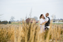 couple standing in a field hugging