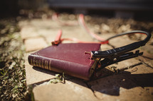 Bible laying on brick sidewalk with jumper cables attached.