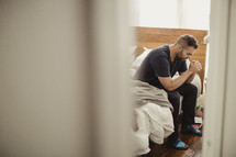 Man sitting on side of bed praying.
