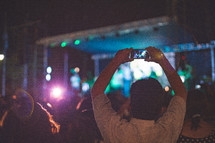 a man taking a picture of a stage with his cellphone at a concert