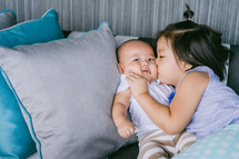 a big sister kissing her baby brother