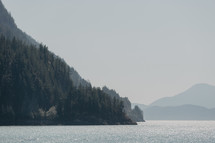rocky shoreline with distant mountains by ocean