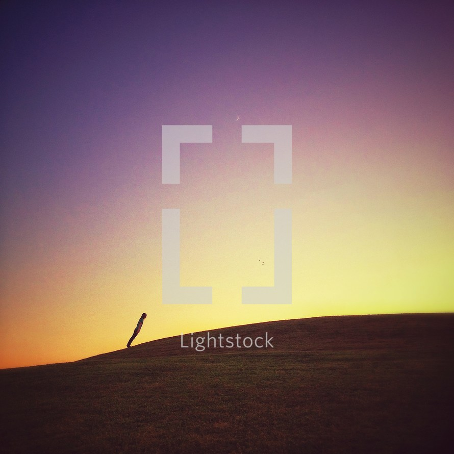 Person leaning forward on top of hill at sunset.