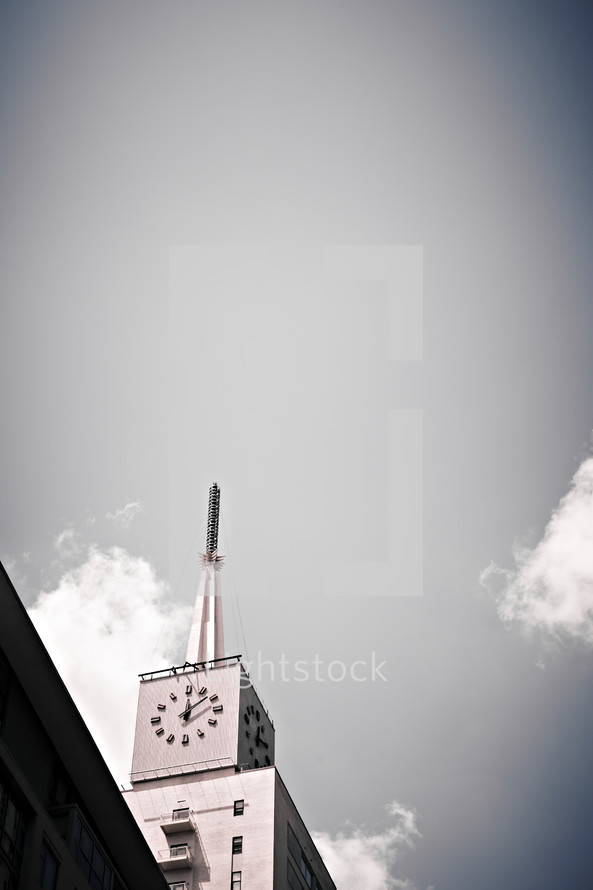 A clock sits high atop a building.