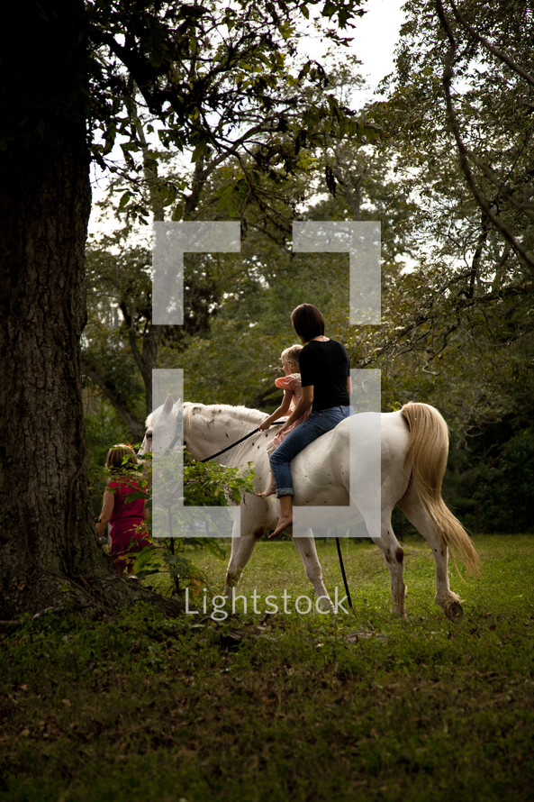 Mother and child riding a horse in forest