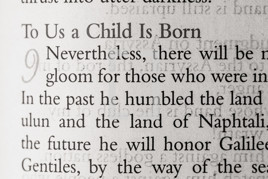 Magnified text of Bible open to Isaiah 9 to us a child is born
